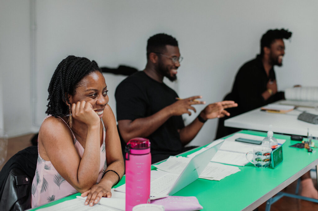 Writer Ifeyinwa Frederick, Director Philip Morris and Assistant Director David Gilbert smile as they sit at a desk during rehearsals.