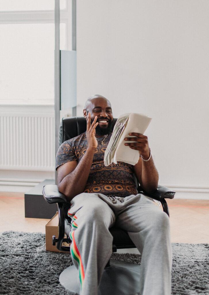 Actor Joseph Black smiles as he looks at his script.