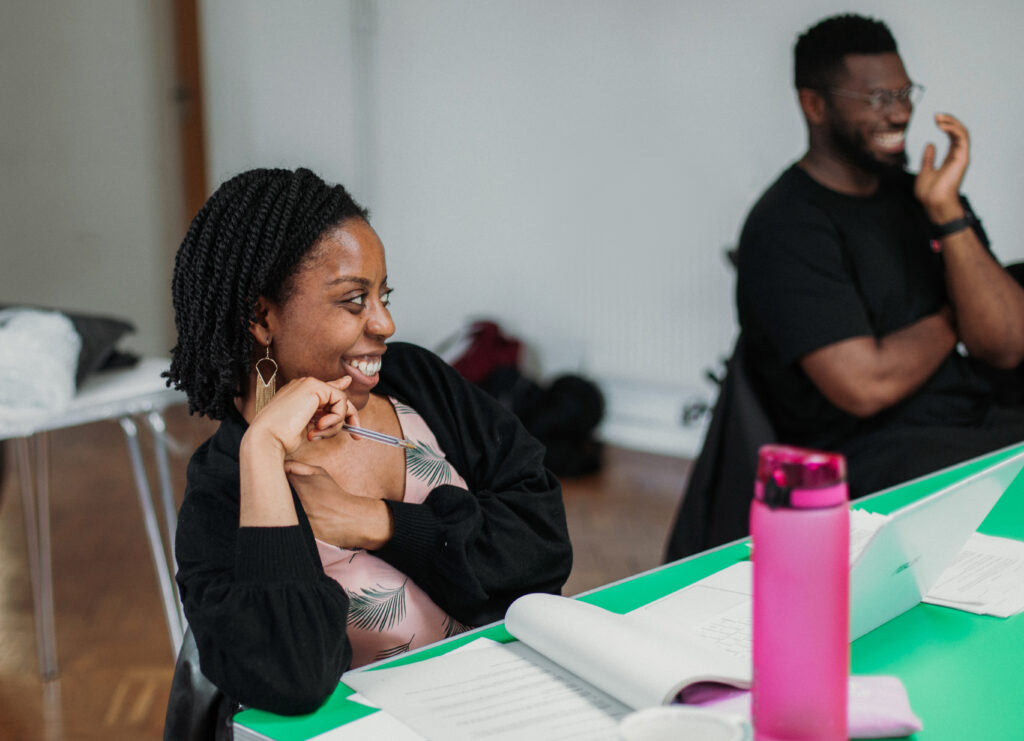 Sessions writer Ifeyinwa Frederick sits at a tavble and watches rehearsals, in front of her on the table is an open script and a bright pink water bottle.