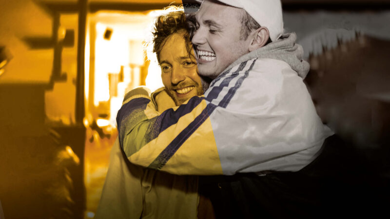 2 men stand hugging in a bar, both have huge smiles. One man wears a baseball cap and tracksuit top, the other man wears a casual jacket.